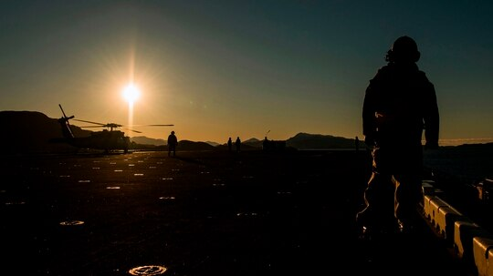 Members of the USS Iwo Jima, a Wasp-class amphibious assault ship, monitor a U.S. Navy helicopter during the NATO exercise Trident Juncture 2018 near Trondheim, Norway, on Oct. 29, 2018. (Jonathan Nackstrand/AFP via Getty Images)