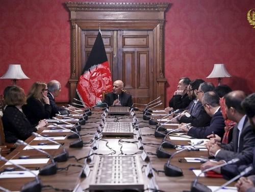 Afghan President Ashraf Ghani, center, speaks to U.S. peace envoy Zalmay Khalilzad, third from left, at the presidential palace in Kabul, Afghanistan, on Monday. (Afghan Presidential Palace via AP)