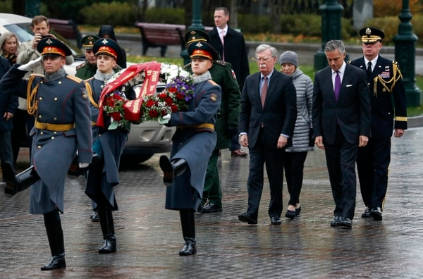 U.S. National Security Adviser John Bolton, fourth from right, walks with U.S. Ambassador to Russia Jon Huntsman, second from right, as they arrive for a wreath laying ceremony at the Tomb of the Unknown Soldier by the Kremlin wall in Moscow, Russia, Tuesday, Oct. 23, 2018. U.S. President Donald Trump's national security adviser Bolton struck a conciliatory note Tuesday in talks in Moscow, just days after Trump vowed to pull out of a key arms control treaty with Russia. (Sergei Karpukhin/Pool Photo via AP)