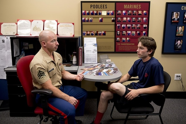 Sgt. Cody Leifheit, a Marine recruiter in Lewiston, Idaho, answers enlistee Brandon Roberts' questions about the Marine Corps at his recruiting office. (Sgt. Reece Lodder/Marine Corps)
