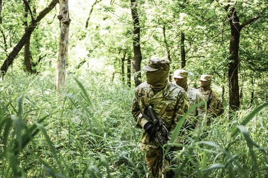 Members of 5th Air Defense Artillery Regiment, patrol in the woods during a day of training at the gas chamber on Fort Sill, Oklahoma, May 14, 2020. Soldiers were required to wear face coverings when not wearing their gas masks. (Sgt. Amanda Hunt/Army)