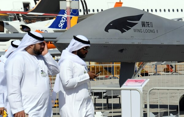 Men walk past a Chinese-made CAIG Wing Loong II medium-altitude, long-endurance UAV, on display during the Dubai Airshow on Nov. 18, 2019. (Karim Sahib/AFP via Getty Images)