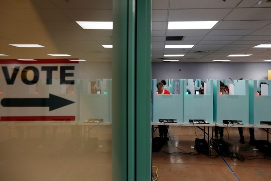 In this Nov. 6, 2018, file photo, people vote at a polling place in Las Vegas. State election officials in at least two dozen states, including Nevada, have seen suspicious cyber activity in the first half of January 2020, although it's unclear who was behind the efforts and no major problems were reported. (AP Photo/John Locher, File)