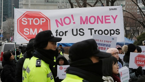 South Korean protesters hold banners during a rally as police officers stand guard near the Foreign Ministry in Seoul, South Korea, Sunday, Feb. 10, 2019. South Korea and the United States struck a new deal Sunday on how much Seoul should pay for the U.S. military presence on its soil, official said, after previous rounds of failed negotiations caused worries about their decades-long alliance. (Lee Jin-man/AP)