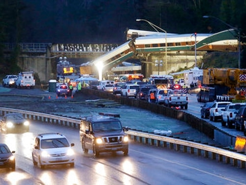 Traffic moves along northbound Interstate 5, left, as southbound lanes are filled with emergency vehicles near the scene of an Amtrak train crash Monday, Dec. 18, 2017, in DuPont, Wash. Tanya Porter, a nurse at Madigan Army Medical Center, was recognized with the Secretary of the Army Award for Valor for helping victims of the crash. (Elaine Thompson/AP)