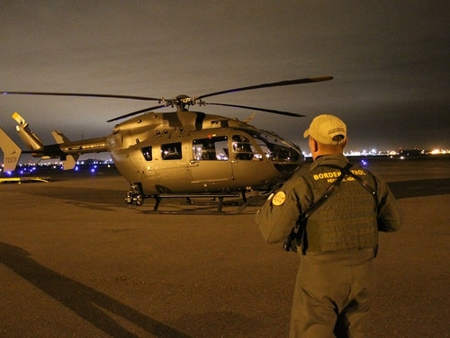A Rio Grande Valley Border Patrol Agent stands in front of a Georgia Army National Guard LUH-72 Lakota before they take off on an aerial detection and monitoring mission on on Jan. 28, 2014, on the U.S. border with Mexico in Texas. (Maj. Will Cox/Georgia Army National Guard)