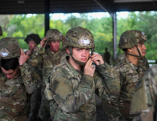 A 82nd Airborne Division paratrooper fastens their helmet before taking part in fall exercises at Fort Bragg, N.C., Aug. 19, 2019. (Senior Airman Cody R. Miller/Air Force)