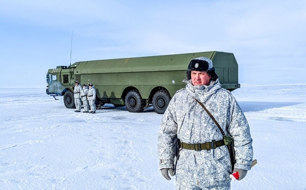 A Russian officer, right, and soldiers stand next to a special military truck at the Russian northern military base on Kotelny island, beyond the Arctic Circle, on April 3, 2019. (Maxime Popov/AFP via Getty Images)