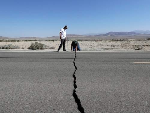 Ron Mikulaco, right, and his nephew, Brad Fernandez, examine a crack caused by an earthquake on Highway 178, Saturday, July 6, 2019, outside of Ridgecrest, Calif. (Marcio Jose Sanchez/AP)