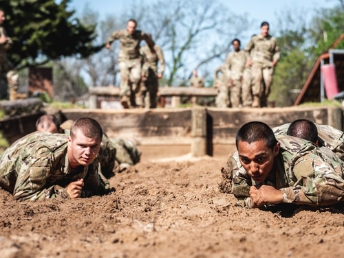 Army recruits at Fort Sill, in Oklahoma, low crawl in sand during an obstacle course at basic combat training on April 23, 2020. (Army)