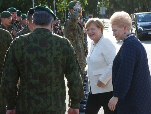 Lithuania's President Dalia Grybauskaite (R) and German Chancellor Angela Merkel arrive for a visit to the NATO enhanced Forward Presence (eFP) battalion battle group on Sept. 14, 2018, in Rukla, Lithuania. (Photo by Petras Maluskas/AFP/Getty Images)