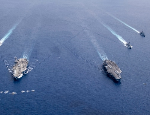 Aircraft from Carrier Air Wings (CVW) 5 and 17 fly in formation over the Nimitz Carrier Strike Force on July 6, 2020, in the South China Sea. The aircraft carriers USS Nimitz (CVN 68), right, and USS Ronald Reagan (CVN 76) and their carrier strike groups are conducting dual carrier operations in the Indo-Pacific as the Nimitz Carrier Strike Force. (MC3Keenan Daniels/Navy)