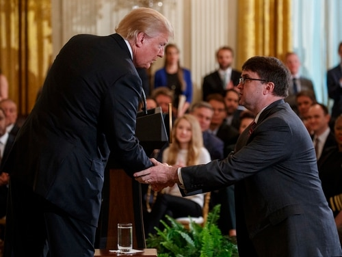 President Donald Trump shakes hands with then acting Veterans Affairs Secretary Robert Wilkie at a White House event on May 18, 2018. The Senate confirmed Wilkie as the next permanent VA secretary on Monday. (Evan Vucci/AP)