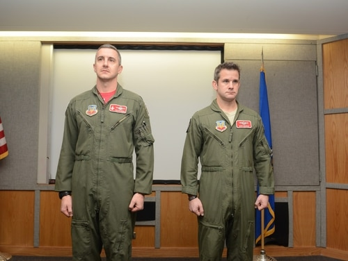 Then-Maj. Adam Kinzinger, 115th Fighter Wing RC-26 Metroliner pilot, right, stands beside Col. Jon Kalberer, 176th Fighter Squadron commander, as the Meritorious Service Medal award package is read during a ceremony at Truax Field, Madison, Wis., March 5, 2016. (Staff Sgt. Andrea F. Rhode/Air National Guard)