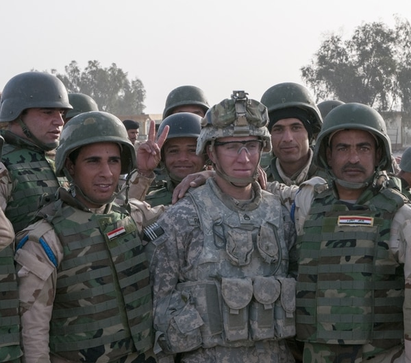 Staff Sgt. Taylor Rouse, a squad leader with 2nd Bn., 34th Armor Regt., 1st ABCT, 1st Inf. Div., poses with Iraqi Army Soldiers following their graduation from a six-week training course Feb. 13 at Camp Taji, Iraq. Rouse and other U.S. Soldiers helped assist the training of more than 1,400 soldiers during the course, developing some personal ties and friendships. (Staff Sgt. Daniel Stoutamire, 1st Inf. Div.)