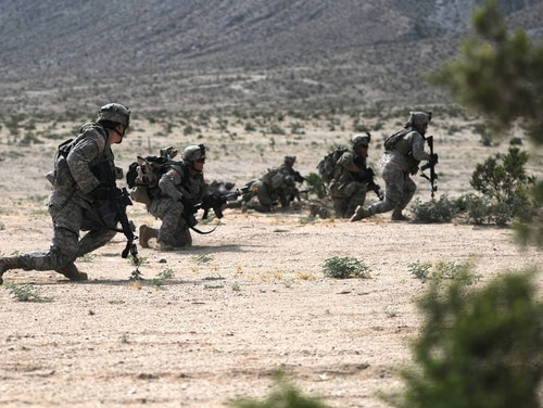 Soldiers of the 155th Armored Brigade Combat Team move forward to assault an enemy held position during a combined arms exercise at the National Training Center at Fort Irwin, California, in May. (Sgt. Edward Lee/Army)