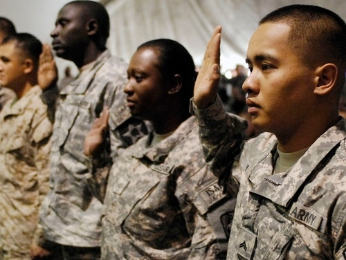 BAGRAM AIRFIELD, Afghanistan -- Army Cpl. Cylee Yagao, a Security Forces team leader for the Khost Provincial Reconstruction Team, along with fellow military Service members take the oath of allegiance during a 2009 naturalization ceremony at Bagram Airfield, Afghanistan. The author discusses his interactions with noncitizen troops while serving as Veterans Affairs secretary. (Senior Airman Felicia Juenke/Air Force)