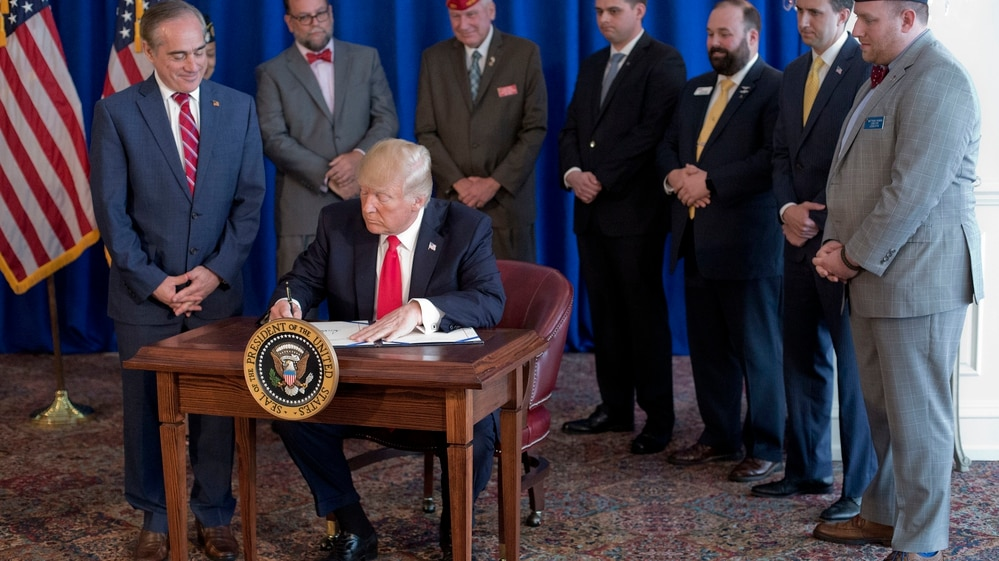 President Donald Trump signs the Veteran's Affairs Choice and Quality Employment Act of 2017 at Trump National Golf Club in Bedminister, N.J., on Aug. 12, 2017. Watching is Veterans Affairs Secretary David Shulkin, left, and standing behind Trump are military veterans. (Pablo Martinez Monsivais/AP)