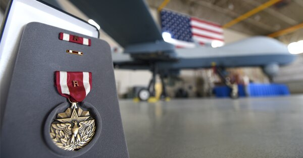 "An Air Force medal with an attached remote ""R"" device sits in front of an MQ-9 Reaper July 9, 2018, at Creech Air Force Base, Nev. (Senior Airman James Thompson/Air Force)"