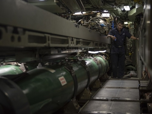 Machinist's Mate (Weapons) 3rd Class Raul E. Bonilla prepares to load one of the fast attack submarine Olympia's Mark 48 Advanced Capability torpedoes for a 2018 sinking exercise in the Pacific Ocean. On Sept. 30, 2019, the Navy announced that sub sailors working as machinist's mates (weapons) would be reclassified as torpedoman's mates. (Mass Communication Specialist 2nd Class Michael H. Lee/Navy)