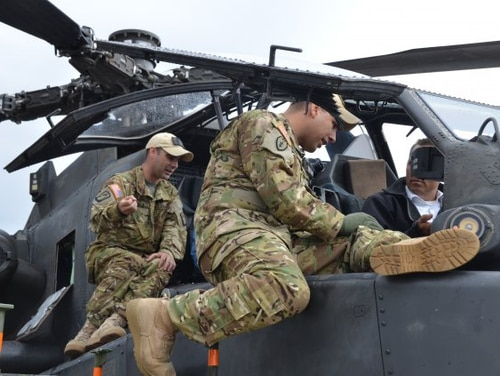 Army Chief Warrant Officer 2 Chad Remala, left, and Chief Warrant Officer 2 Victor Reyna, both pilots with the Army's 12th Combat Aviation Brigade, describe the instruments in the AH-64 Apache helicopter cockpit to former German army reservists visiting Katterbach Army Airfield at U.S. Army Garrison Ansbach, Germany, in 2015. The Army allows warrant officers to fly helicopters, and the Air Force is trying to decide whether to re-institute its own warrant officer program. (Army)