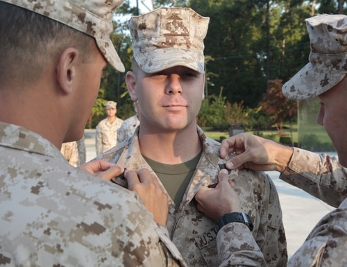 U.S. Marine Corps Staff Sgt. Harold Rivera, Assistant Training Chief S-3, Headquarters and Service Company, Marine Corps Combat Service Support Schools (MCCSSS), stands at attention while he is pinned on the rank of Gunnery Sergeant during his promotion ceremony at the Vietnam Memorial, Jacksonville, N.C., Sept. 4, 2013. (U.S. Marine Corps Combat Camera photo by Sergeant Mark E. Morrow/Released)