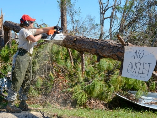 Staff Sgt. Colleen Curren, structures journeyman from the 202nd Rapid Engineer Deployable Heavy Operational Repair Squadron Engineer out of Camp Blanding, Fla., cuts a fallen tree on Debi Road in the Bayou George area of Panama City Oct. 14. The Red Horse unit was called in after Hurricane Michael because of its members' expertise in efficient route clearing. (Staff Sgt. Carlynne DeVine/Air National Guard)