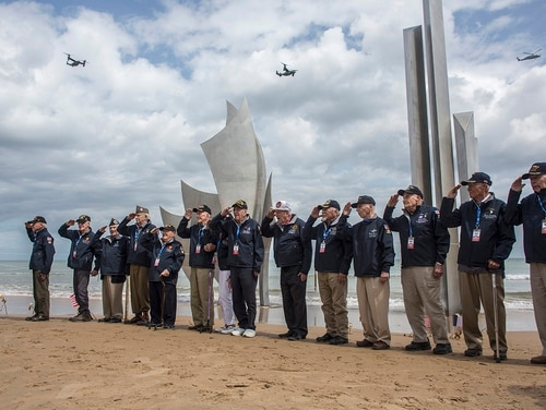 World War II veterans from the United States salute as they pose in front of Les Braves monument at Omaha Beach in Saint-Laurent-sur-Mer, Normandy, France, Monday, June 3, 2019. France is preparing to mark the 75th anniversary of the D-Day invasion which took place on June 6, 1944. (Rafael Yaghobzadeh/AP)