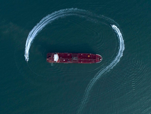 In this July 21 aerial view photo, a speedboat of Iran's Revolutionary Guard maneuvers around the British-flagged oil tanker Stena Impero which was seized in the Strait of Hormuz on Friday . (Morteza Akhoondi/Tasnim News Agency via AP)