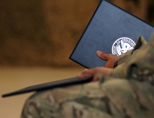 A soldier holds onto his certificate he received from the U.S. Department of Homeland Security during a naturalization ceremony on Kandahar Airfield, Afghanistan, on Feb. 10, 2012. (Sgt. Amanda M. Hils/Army)