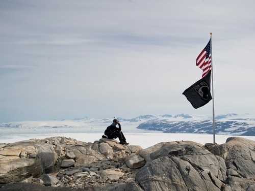 Then-Lt. Cmdr. Robert Tucker, from the Coast Guard's office of aviation forces, provides an operation status and position report to the Atlantic Area Command Center about the J2F-4 Grumman Duck mission on a glacier near Koge Bay, Greenland, Aug. 1, 2013. (Coast Guard)