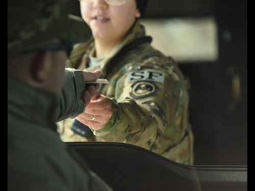 A 28th Security Forces Squadron response force member hands an airman back his common access card after scanning it at the gate to Ellsworth Air Force Base, S.D., Dec. 4, 2018. (2nd Lt. Joshua Sinclair/Air Force)