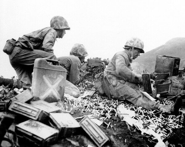 "Original caption from 1945: These Marines of the Fifth Division never saw as much ""brass"" in their entire time in ""boot camp"" as they have around their machine gun on Iwo Jima, Japan on March 5, 1945. The battle of Suribachi wasn't a dry run and they didn't have to pick up their ""brass"" as the battle was for keeps. (AP Photo)"