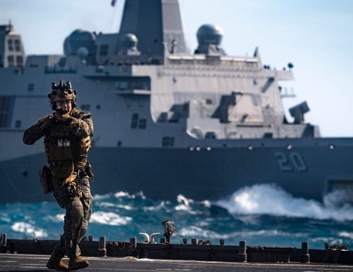 A Force Reconnaissance Marine with the 31st Marine Expeditionary Unit clears the flight deck of the amphibious dock landing ship Ashland (LSD 48) during a visit, board, search and seizure training exercise with the amphibious transport dock ship Green Bay (LPD 20). (Mass Communication Specialist 2nd Class Markus Castaneda/Navy)
