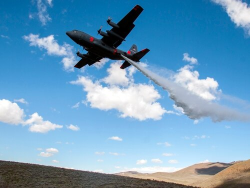A C-130 with the 152nd Airlift Wing, Nevada Air National Guard, drops water in the mountains east of Boise, Idaho as part of the annual Modular Airborne Fire Fighting System training and certification, April 21, 2017. (Tech. Sgt. Emerson Marcus/Air Force)