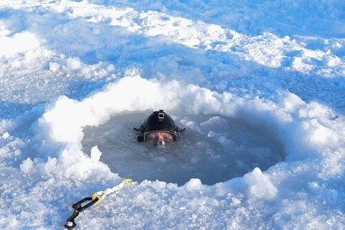 Chief Hospital Corpsman Kristopher Mandaro, assigned to Underwater Construction Team One, surfaces from a waterhole during a torpedo exercise in the Arctic Circle. (MC1 Daniel Hinton/Navy)