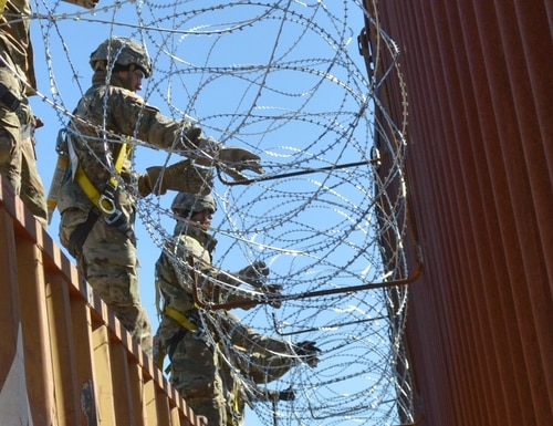 Soldiers assigned to 515th Engineer Company and 65th Military Police Company place concertina wire on a border wall in Sasabe, Ariz., on Feb. 7, 2019. (Sgt. 1st Class TaWanna Starks/U.S. Army)