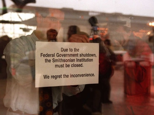 WASHINGTON, : An employee of the National Air and Space Museum in Washington, DC hangs a sign on the door 14 November explaining the reason for the museum closure. The US government, which ran out of money midnight Tuesday, sent nearly 800,000