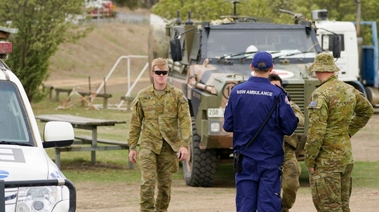 Australian Army personnel and an ambulance officer gather near the scene of a downed fire tanker aircraft Jan. 23 in Cooma, Australia. Three American firefighters died after their C-130 crashed while battling a bush fire in New South Wales. (Mark Evans/Getty Images)
