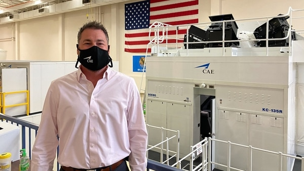 Dan Gelston, Group President of CAE's Defence & Security Group, poses in front of a company simulator. (CAE)