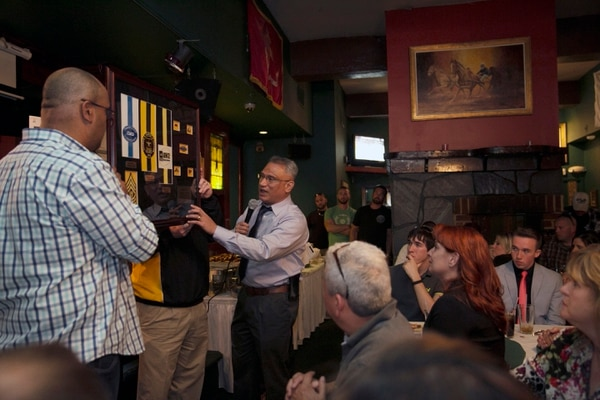 Sgt. Maj. Patrick Fatuesi presents a plaque to the family of retired Command Sgt. major Robert Gallagher during a celebration of his life at Murphy's Grand Irish Pub in Alexandria, Va., on Sunday, April 26, 2015. Gallagher, 52, who died in October, 2014 and fought in Panama, Somalia and Iraq, was buried at Arlington National Cemetery. (Mike Morones/Staff)