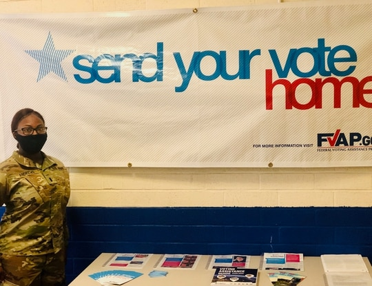 Army 1st. Lt. Chavonda Andrews, Voting Assistance Officer for 120th Adjutant General Battalion, stands next to a static voting information display in the battalion's building. (Sgt. Cierra Quinn/Army).