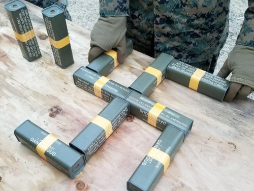 Military explosives arranged in the shape of a swastika. (Screenshot of Tweet from Twitter account @Jacobite_Edward)