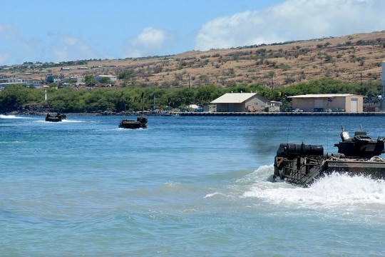 Amphibious assault vehicles launch from the beach, transporting a unit of Marines to the amphibious assault ship Peleliu (LHA 5), while underway for Rim of the Pacific Exercise 2014. (Mass Communication Specialist 3rd Class Dustin Knight/Navy)