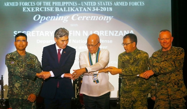 Philippine Defense Secretary Delfin Lorenzana, center, U.S. Ambassador to the Philippines Sung Kim, second left, Philippine Armed Forces Chief Lt. Gen. Carlito Galvez, second right, Lt. Gen. Lawrence Nicholson, right, commander of the 3rd U.S. Marine Expeditionary Forces, and Northern Luzon commander Lt. Gen. Emmanuel Salamat link arms during the opening ceremony of the Joint U.S.-Philippines military exercise dubbed