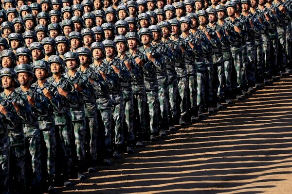 In this photo released by China's Xinhua News Agency, Chinese People's Liberation Army (PLA) troops march in formation Sunday, July 30, 2017, as they arrive for a military parade to commemorate the 90th anniversary of the founding of the PLA on Aug. 1 at Zhurihe training base in north China's Inner Mongolia Autonomous Region. (Ju Zhenhua/Xinhua via AP)