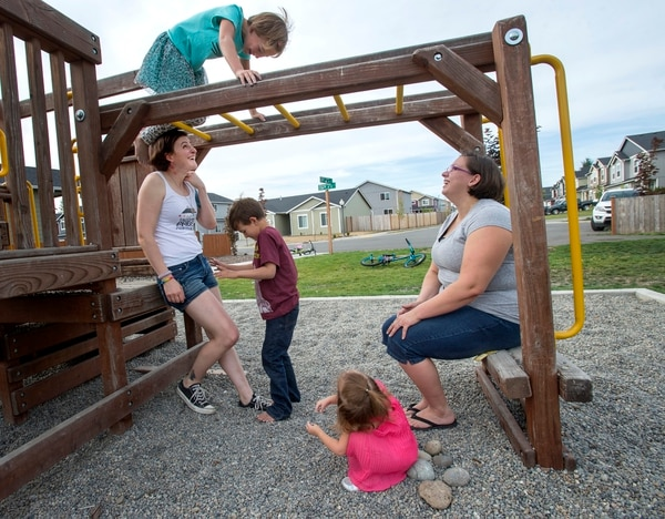 In this photo taken on Aug. 28, 2015, Capt. Jennifer Peace, left, and her spouse, Deborah, enjoy hanging out with their kids at a playground near their home in Spanaway, Wash. Peace is one of an estimated 15,000 transgender people who serve in the active-duty military. She's speaking out in the hopes of helping people understand transgender men and women. (Drew Perine/The News Tribune via AP)