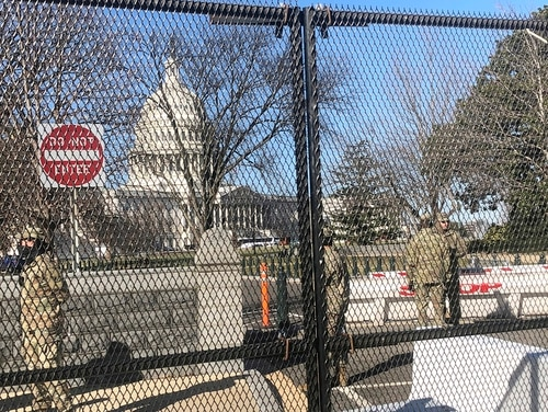 Members of the National Guard stand inside anti-scaling fencing that surrounds the Capitol, Sunday, Jan. 10, 2021, in Washington. (Alan Fram/AP)