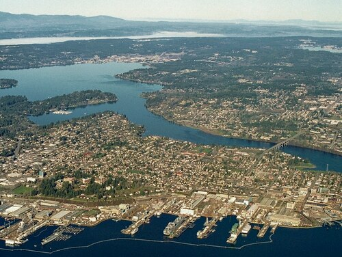 Puget Sound Naval Shipyard and the downtown Bremerton waterfront are viewed from over Port Orchard looking west. The waterways Sinclair Inlet, Port Washington Narrows and Dyes Inlet are visible, with the Olympic Mountains in the background. (Defense Logistics Agency Land and Maritime)