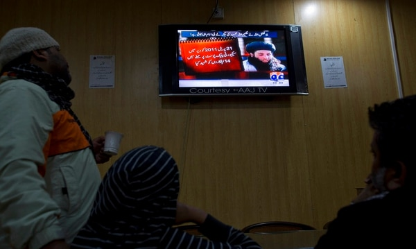 In this Nov. 7, 2013, file photo, people watch a news report on TV about newly selected leader of Pakistani Taliban leader Mullah Fazlullah at a coffee shop in Islamabad, Pakistan. An Afghan defense ministry official says Friday, June 15, 2018, a US drone strike in northeastern Kunar province killed Fazlullah. (B.K. Bangash/AP)